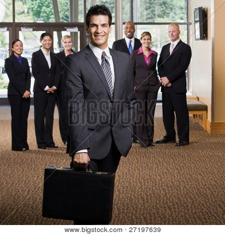 Confident businessman holding briefcase in front of co-workers