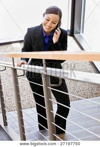 High angle view of Asian businesswoman talking on cell phone and ascending stairs