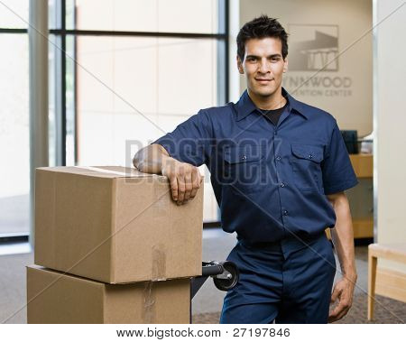 Delivery man in uniform posing with stack of cardboard boxes