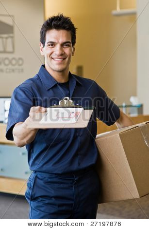 Friendly delivery man in uniform presenting shipping receipt and holding cardboard box
