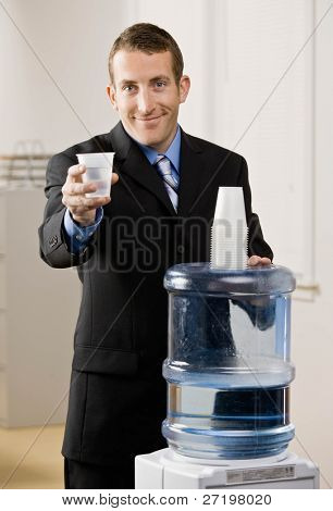 Thirsty businessman filling cup from water cooler