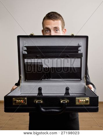 Worried businessman opening empty briefcase