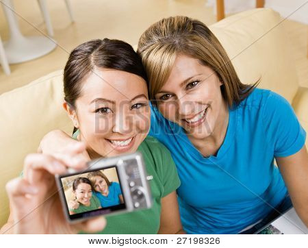 Happy friends taking self-portrait with digital camera