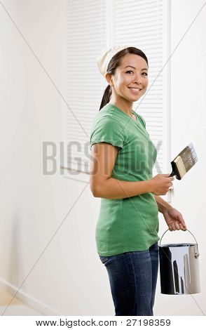Self-sufficient woman painting with paint brush and renovating home