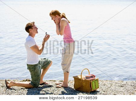 Boyfriend proposing to girlfriend near stream