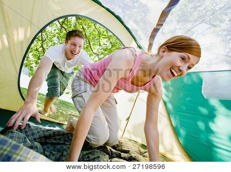 Couple climbing into tent