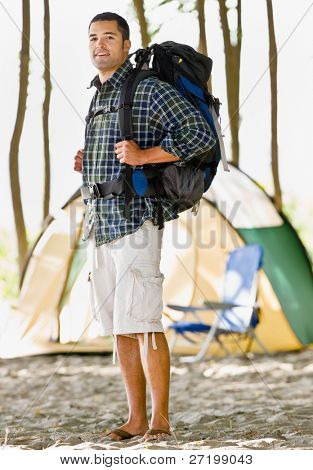 Man carrying backpack at campsite