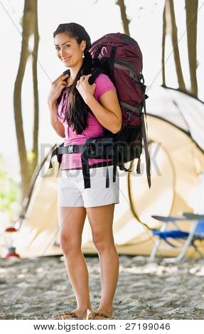 Woman carrying backpack at campsite