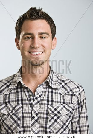 A young man wearing a plaid shirt is smiling at the camera.