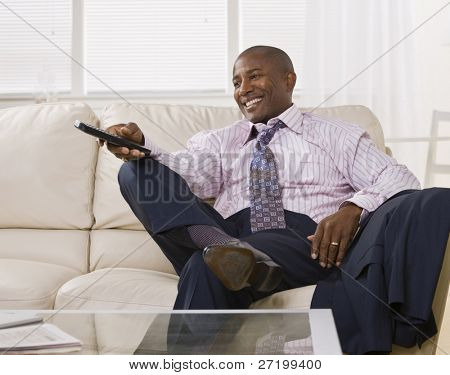 Attractive African America watching TV and laughing, while sitting on a coach dressed in a shirt and tie. square