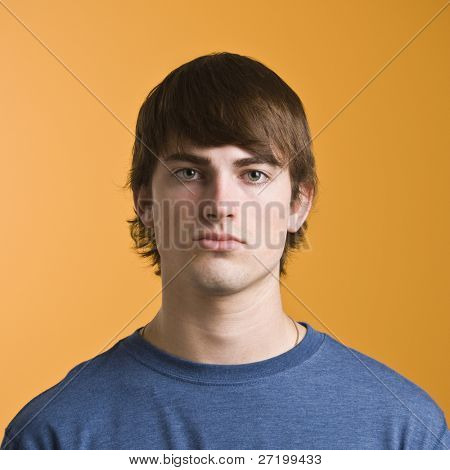 Attractive male headshot with long bangs and blue shirt. vertical