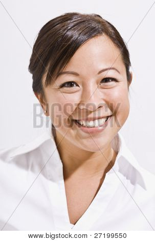 A headshot of an attractive young asian woman.  She is smiling directly at the camera. Vertically framed shot.