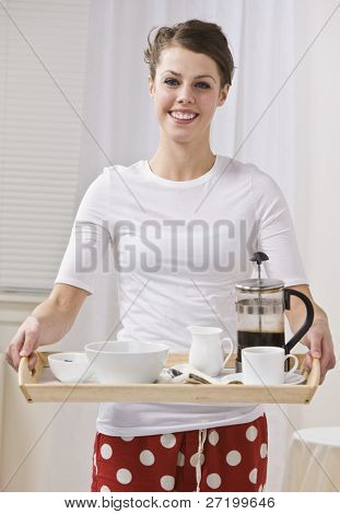 Attractive woman serving coffee in a french press. She is smiling and looking at the camera. Vertically Framed Photo.
