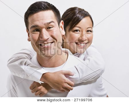 An attractive young couple posing together.  They are smiling directly at the camera.  Horizontally framed shot.