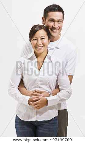 A happy young couple posing together.  They are smiling at the camera.  Vertically framed shot.