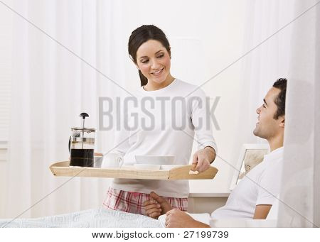 A beautiful young woman serving a breakfast tray to a man lying in bed.  They are smiling happily at one another. Horizontally framed shot.