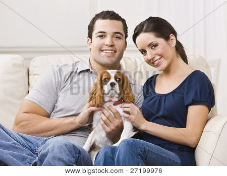 Attractive couple with their dog on their living room couch. horizontal