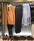 Men clothes row of clothes, suit, jacket, shoes,shirts on the racks in clothing store    poster