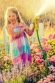 Playful girl watering flowers with rain in the garden at summer day. Child using garden hose on sunn poster