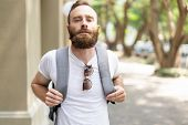 Relaxed Bearded Guy Enjoying Vacation. Tired Young Man Wearing Summer Clothes, Carrying Heavy Backpa poster