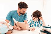 Little Boy In Glasses Doing Homework With Father. Education At Home. White Table In Room. Sitting Bo poster