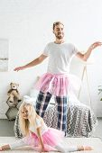 Happy Father And Daughter In Pink Tutu Skirts Having Fun And Dancing Together At Home poster