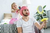 Adorable Little Daughter In Tutu Skirt Playing With Father In Pink Wig Looking At Mirror poster
