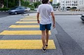 Young Man On Pedestrian Crossing, Back View. Busy City Street, Concept Of Pedestrian Safety On The R poster