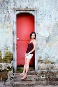 Girl leans in red doorway