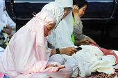 JAKARTA, INDONESIA - SEPTEMBER 20: Muslim girls send text messages on mobile phones between prayers