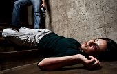 Battered woman lies lifelessly at the bottom of stairs with a faceless man holding a belt, a conceptual shoot portraying the process and effects of domestic violence poster