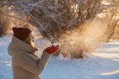 Winter Holiday, Fun And People Concept - Young Woman In Red Winter Hat Blowing Snow From Red Mittens poster