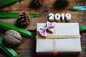 2019 Eco Friendly Brown Wrap Gift Box On Old Wooden Table Background, Happy New Year Gift Concept poster