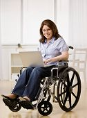 Disabled woman sitting in wheel chair typing on laptop
