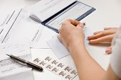 picture of stomp  - Woman writing checks from checkbook to pay monthly bills and stamping return envelope - JPG