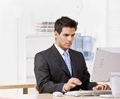Serious businessman typing on computer
