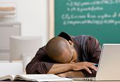 Exhausted teacher laying on desk in school classroom