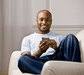 Relaxed man using electronic organizer in livingroom