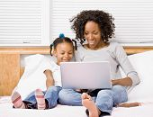 Mother and daughter typing on laptop on bed in bedroom