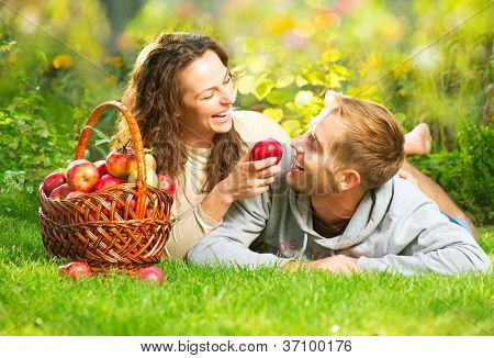 Happy Couple in Autumn Garden.Having Fun on the Grass and Eating Apples Healthy Food.Outdoor.Park.Basket of Apples.Harvest concept. Diet