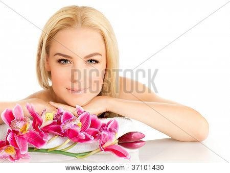 Image of happy beautiful adult girl in spa salon, attractive blonde female enjoying dayspa, pretty woman isolated on white background with pink orchid flowers, healthy lifestyle, zen and spa concept