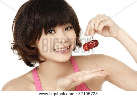 Asian young woman holding cherryes, close up, looking at camera, studio on white