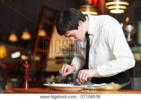 man waiter in uniform preparing fish food on plates at restaurant