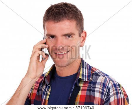 Smiling casual young man using his phone while looking at the camera, isolated on white