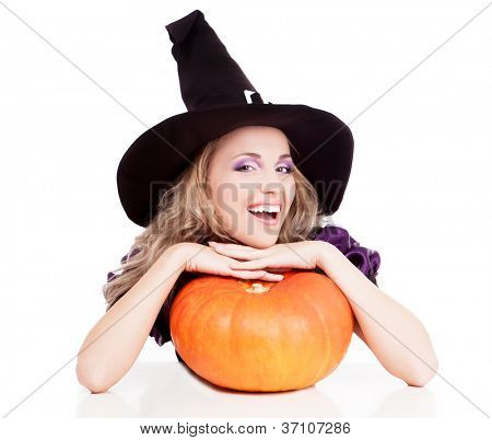 happy young witch with a pumpkin sitting by the table, isolated on white background