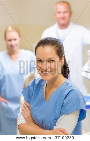Smiling dental hygienist woman with stomatology team of medical professionals