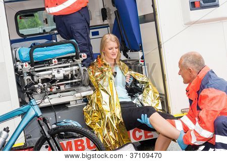 Emergency paramedics with woman bike accident in ambulance help injury