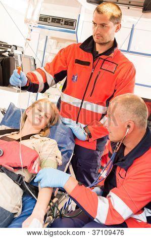 Unconscious patient woman emergency ambulance paramedics measuring blood pressure