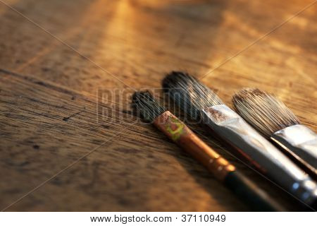 Painting brushes on an old painters desk.
