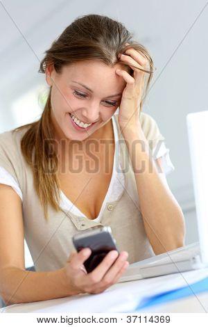 Jovem feliz em ler a mensagem no telefone